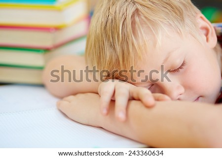 Tired little schoolboy taking nap - stock photo