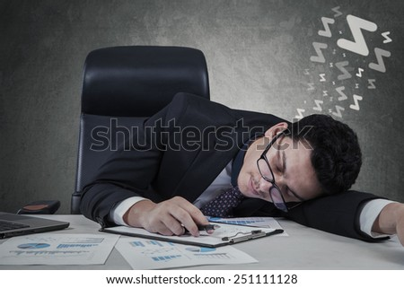 Tired male entrepreneur sleeping on desk with paperwork at workplace - stock photo
