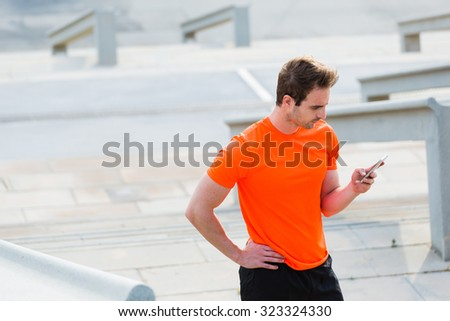 Tired male jogger dressed in orange active shirt with copy space for your brand chatting on his mobile phone,young fit men reading message on cell telephone while taking break between workout outdoors - stock photo