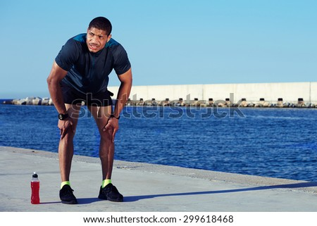 Tired male runner took a break after hard workout outdoors standing on sea and sky background with copy space area for your text message or information, sweaty sportsman having rest leaning on knees - stock photo