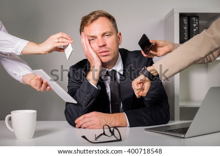 Tired man being overloaded at work  - stock photo