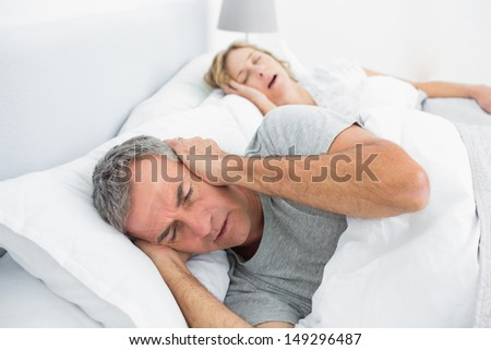 Tired man blocking his ears from noise of wife snoring in bedroom at home