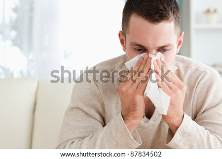 Tired man blowing his nose in his living room - stock photo