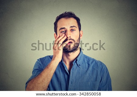Tired man. Closeup portrait of a groggy upset worried sad, depressed guy with a headache isolated on gray background. Negative human emotion face expression reaction  - stock photo