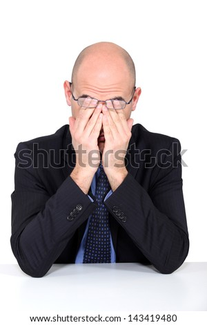 Tired man rubbing his eyes - stock photo