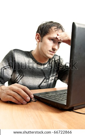 tired man sits at a table and sadly looks at the laptop screen having taken hand in head. Works at laptop computer at home