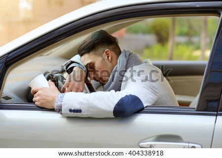 tired man sleeping behind the wheel of a car with a cup in his hand - stock photo
