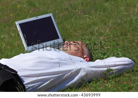 Tired man sleeping in a field near his laptop.