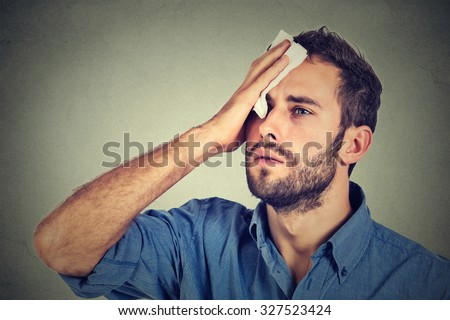 Tired man stressed sweating having fever headache isolated on gray wall background. Worried guy wipes sweat on his face - stock photo