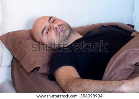 tired man with a beard who sleeps in bed - stock photo