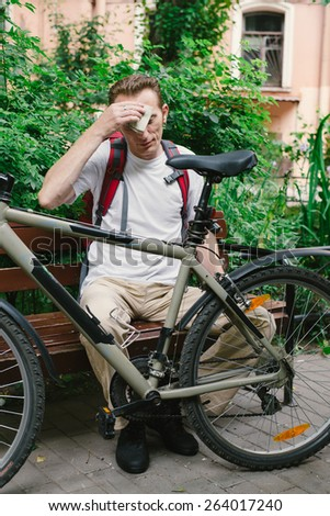 tired man with bike wipe the forehead at the park bench - stock photo