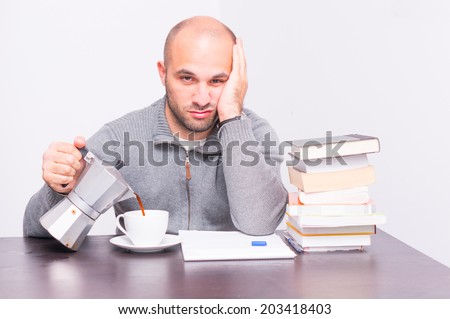 Tired man with books drinking coffee