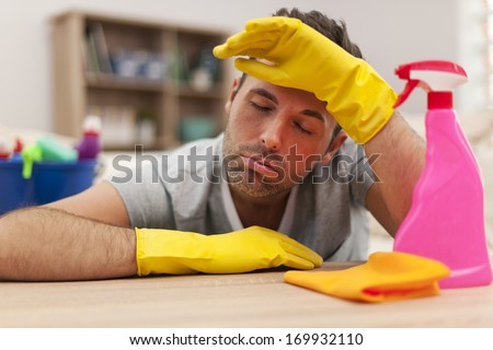 Tired man with cleaning equipment - stock photo