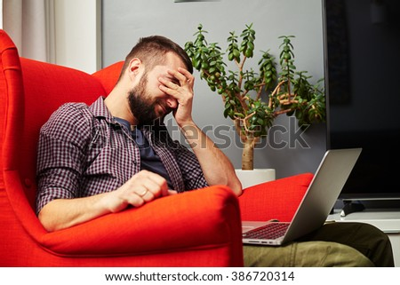 tired man with laptop on knees at home