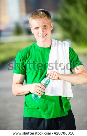 Tired man with white towel drinking water from a plastic bottle after fitness time and exercising in city street park at beautiful summer day. Sporty model caucasian ethnicity training outdoor.  - stock photo
