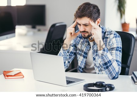 Tired man working on the laptop in the office. Business man wearing casual clothes thinking about a problem at his computer - stock photo