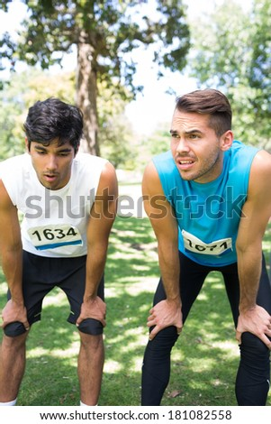 Tired marathon runners with hands on knees standing in park - stock photo