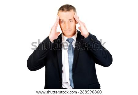 Tired mature businessman suffering from headache. - stock photo