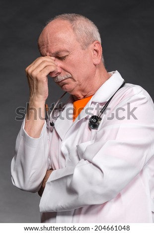 Tired medical doctor with stethoscope on a gray background