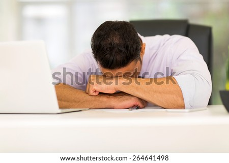 tired middle aged businessman sleeping at work - stock photo