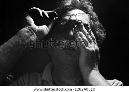 tired middle-aged man rubs his eyes< black and white - stock photo