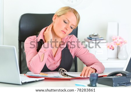 Tired modern business woman sitting at office desk and working with financial documents - stock photo