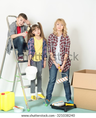 Tired mother and children makes repairs at home. - stock photo