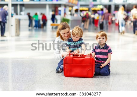 Tired mother and two little sibling kids boys at the airport, traveling together. Angry family waiting. Canceled flight due to pilot strike.