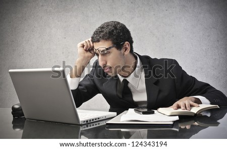 Tired mulatto businessman using a laptop computer - stock photo
