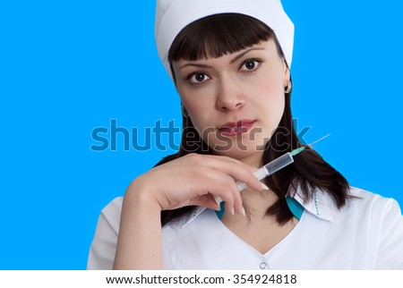 Tired nurse with syringe on blue background - stock photo
