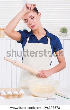 Tired of cooking. Tired young woman in apron holding rolling pin and touching her forehead with hand while standing in a kitchen - stock photo