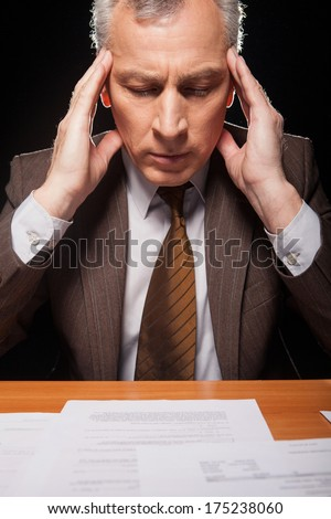 Tired of paperwork. Senior man in formalwear sitting at his working place and holding head in hands while isolated on black background  - stock photo
