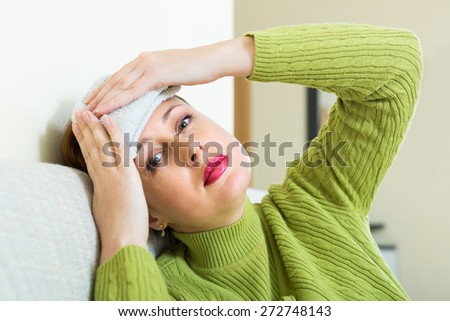 Tired of problems woman sitting on sofa with intense headache