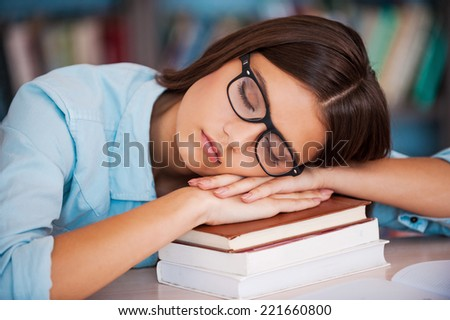 Tired of studying. Tired young women holding her head on the book stack and sleeping while sitting at the library desk - stock photo