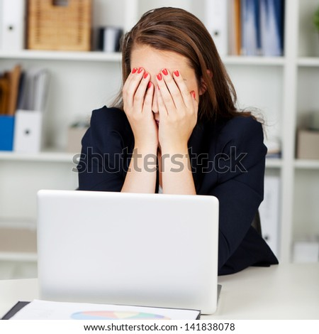 Tired or depressed businesswoman sitting at her desk behind her laptop with her hands covering her eyes - stock photo