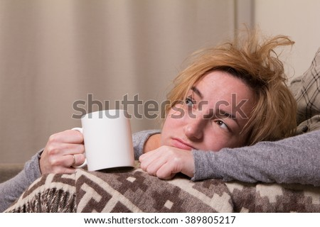 tired or ill girl lie on brown divan and grown plaid and hold white mug