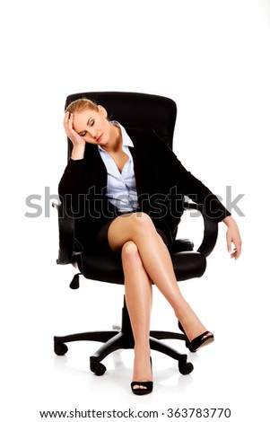Tired or worried business woman sitting on armchair - stock photo
