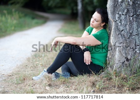 Tired overweight woman sitting by the tree after training - stock photo