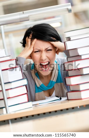 Tired pretty woman with headache sitting at the desk surrounded with piles of books - stock photo