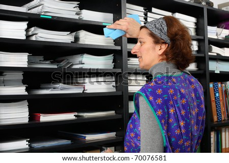 Tired professional cleaning lady at her work in the office