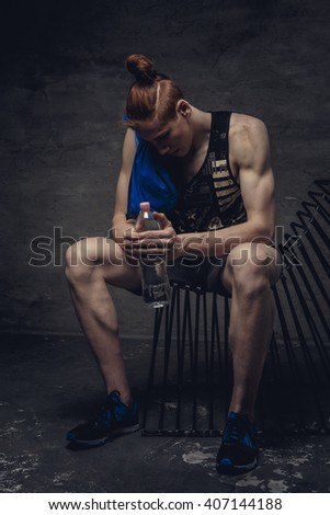 Tired redhead sporty man relaxing on a chair.