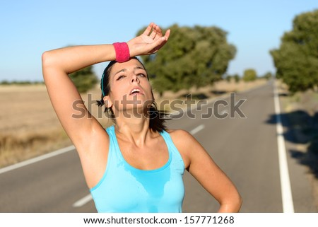 Tired runner sweating after running hard in countryside road. Exhausted sweaty woman after marathon training on hot summer. Hispanic brunette female athlete outdoors. - stock photo