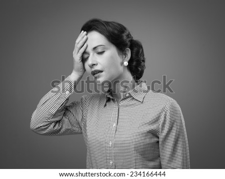 Tired 1950s style woman touching her foehead with mouth open - stock photo