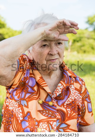 Tired sad old woman on nature background - stock photo
