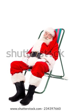 Tired santa sitting on a chair and relaxing - stock photo