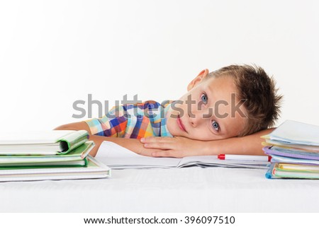 Tired school boy is dreaming on desk - stock photo