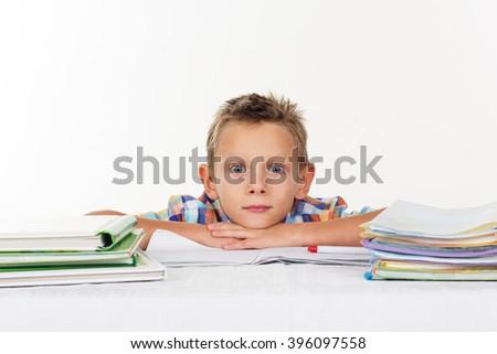 Tired school boy thinking lying on table - stock photo