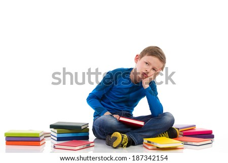 Tired schoolboy. Sad schoolboy sitting on the floor with colorful books. Full length studio shot isolated on white. - stock photo