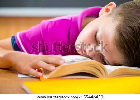Tired schoolboy sleeping on book in classroom - stock photo