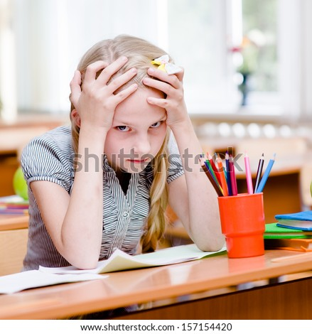 tired schoolgirl in classroom. looking at camera - stock photo